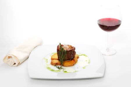 roast meat with potatoes on white plate with glass of wine photo