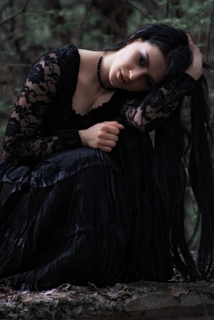 sad woman in old style black dress. outdoor shot photo