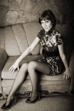 attractive woman sitting on sofa. indoor shot photo