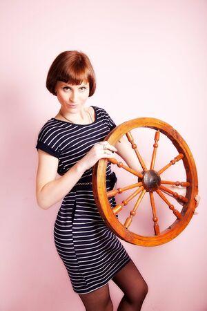 portrait of attractive woman with wooden wheel. indoor shot photo
