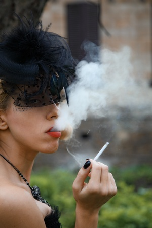 smoking woman in old style black dress. outdoor shot photo