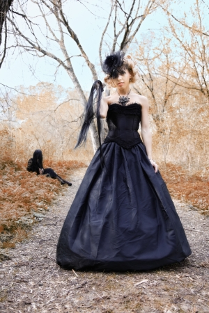 black and white lock: aggrassive woman in old style black dress. outdoor shot