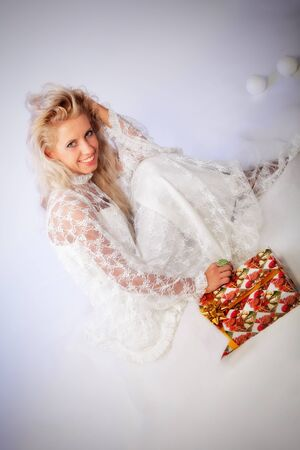portrait of attractive young woman with giftbox. indoor shot photo