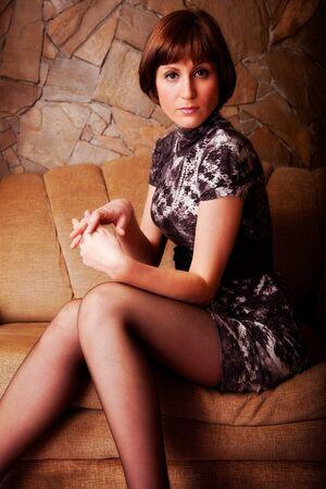indoor shot: atractiva mujer sentada en sof� tiro interior