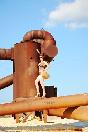 bikini construction: attractive woman on rusty old metal construction