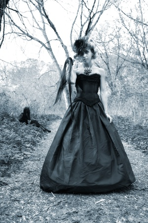 aggrassive woman in old style black dress. outdoor shot photo