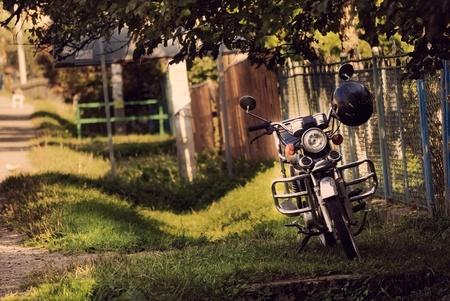 motorbike near fence in village photo