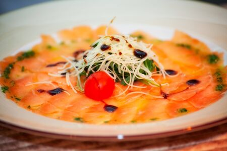 carpaccio. salmon with salad arugula and cheese photo