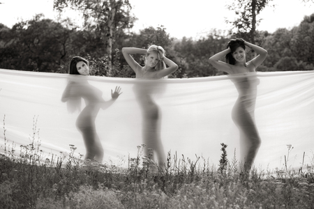 three girls wrapped in white fabric. outdoor shot Stock Photo