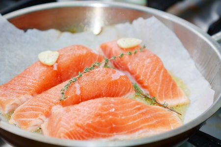 raw salmon with spices on pan photo