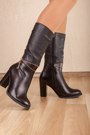 A boots with beautiful legs on wood Stock Photo