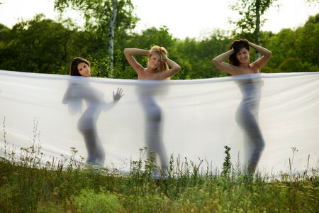 three girls wrapped in white fabric. outdoor shot photo