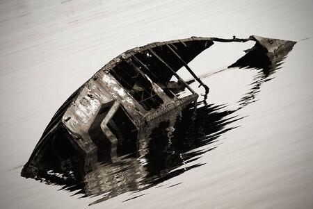sunken boat: rusty sunken boat in ripples water Stock Photo