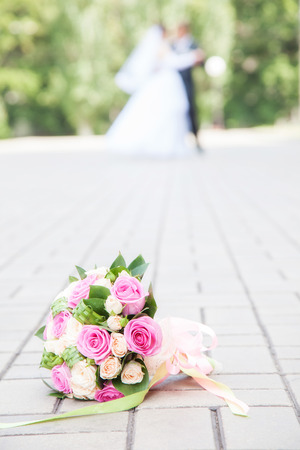 bouquet on the floor. against the background of newlyweds dance photo