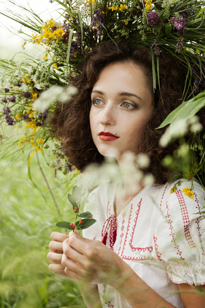 attractive girl in a meadow with a wreath photo