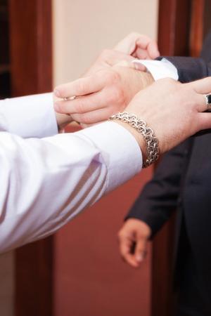 corrects each cuff groom. hands photo