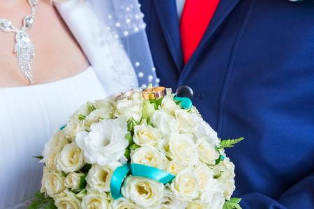 bruidsboeket: kleine bruidsboeket in de handen en ringen op Stockfoto