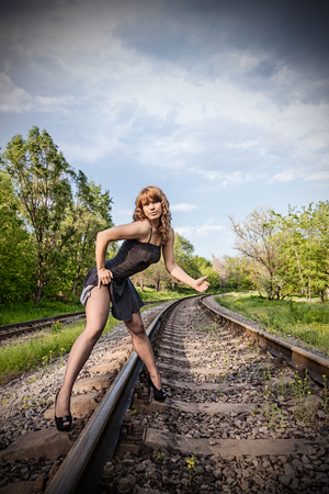attractive girl hitchhiking on rail photo