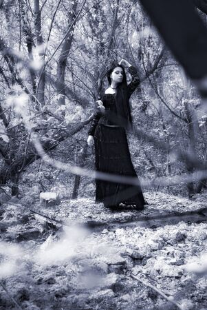 attractive woman in old style black dress. outdoor shot photo