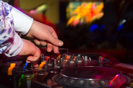 control panel lights: DJ hands on the remote. nightclub