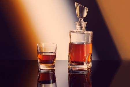 bottle and glass of whiskey on gradient background photo