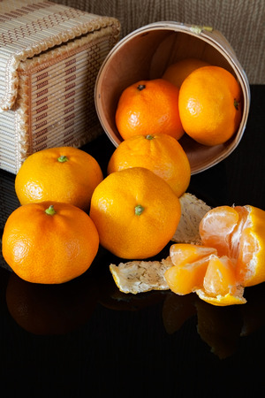 c vitamin: many tangerine on background wicker boxes with reflection Stock Photo