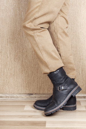 Mens leather shoes and jeans khaki legs. A man stands on a wooden floor near the wall.