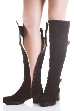 pies sexis: Hermosas piernas femeninas en botas de ante negro sobre un fondo blanco Foto de archivo
