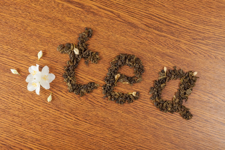 redolence: the word tea from leaves of green tea on a wooden surface near jasmine flowers