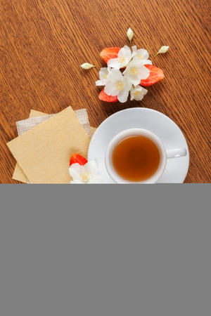 redolence: white cup of green tea. jasmine flowers with strawberry halves. texture blank for writing. still life
