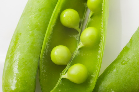 disclosed: disclosed several pods of green peas on a white plate. close-up Stock Photo