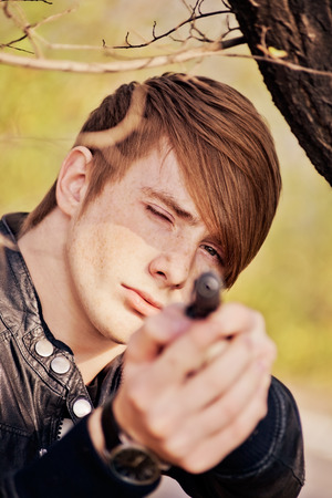 beautiful boys: attractive, aggressive red-haired guy with a gun in nature. close-up portrait