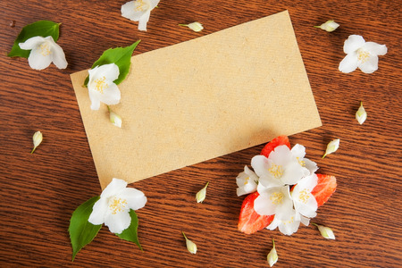 redolence: card on a wooden surface with jasmine flowers and strawberries. background
