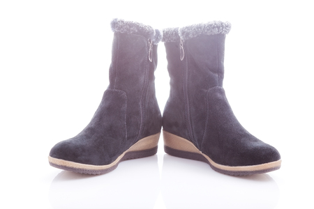 heel strap: Beautiful, black boots with zips and buckles made of suede. On a white background.