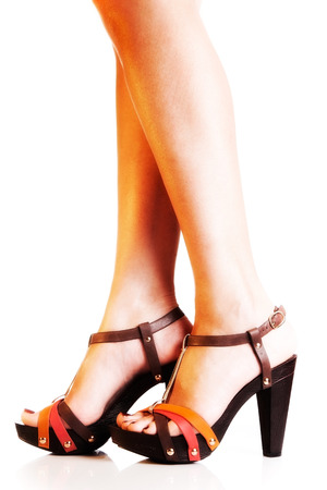 ankle strap: Beautiful female sandals on slender legs. Isolated on white Stock Photo