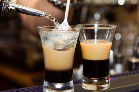 baileys: B-52 Preparation of three-layered drink. close-up Stock Photo
