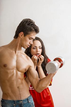 hombre deportista: hombre atractivo y el tren emocionalmente mujer con pesas Foto de archivo