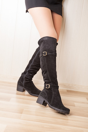 jackboot: A boots with beautiful legs on wood Stock Photo