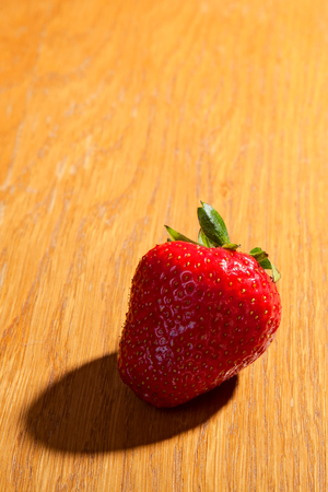 beautiful, juicy, ripe strawberry on a wooden surface. fruit background