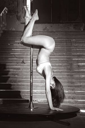 Beautiful brunette dancing on a pole on underground background. Stock Photo