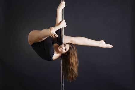 Beautiful brunette dancing on a pole Фото со стока