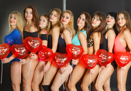 sexy girl dance: Beautiful women with red hearts on a pole. Balloons with non-English text  translated as I love you