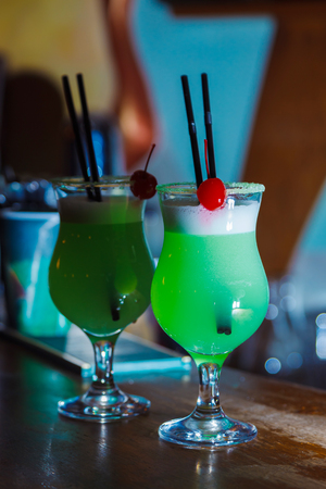 A beautiful green cocktail with white foam and cherry in a tall glass. close-up
