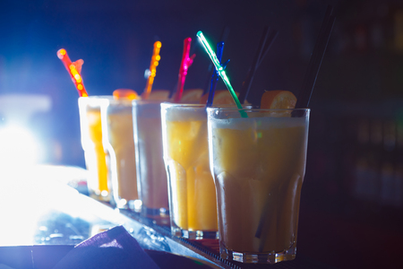 A beautiful yellow cocktails with slice of orange in a tall glasses. close-up
