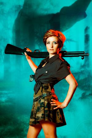 Portrait of attractive woman in military style holding gun in hands