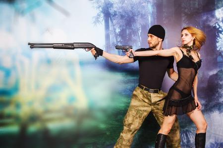 militaire sexy: homme sérieux et jolies femmes dans un style militaire avec arme