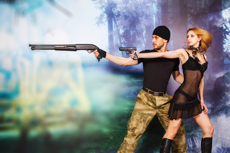 serious man and attractive women in military style with weapon Stock Photo