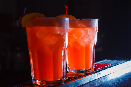 A beautiful red cocktails with slice of orange and cherry in a tall glasses. close-up Stock Photo