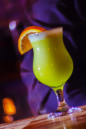 A beautiful yellow cocktail with white foam and orange slice in a tall glass. close-up Stock Photo