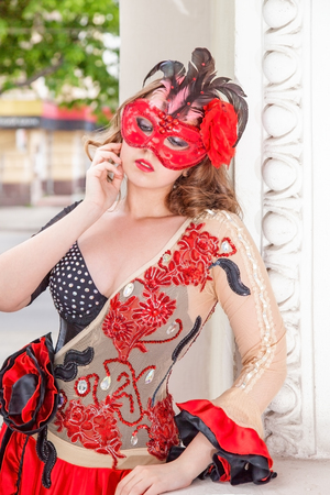 Portrait of attractive blonde woman in red mask